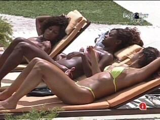 As meninas conversam enquanto tomam sol à beira da piscina