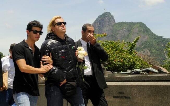 João Baptista, filho adotivo de Lily Marinho, é amparado por amigos durante o enterro