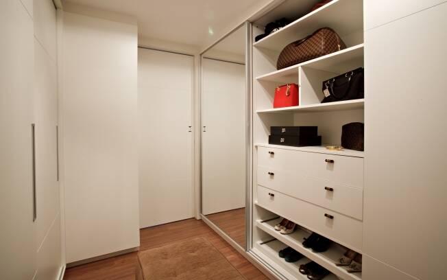 Um pequeno corredor otimiza a circulação e o pufe central ajuda nas trocas de roupa