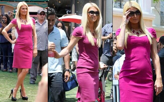 Com um vestido justo e cor-de-rosa, Paris Hilton surpreendeu com a barriguinha