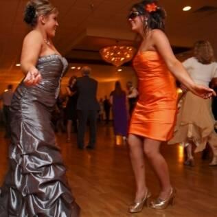 Ashley, de laranja, dança com uma amiga. Ela gastou mais de 200 dólares em preparativos para a