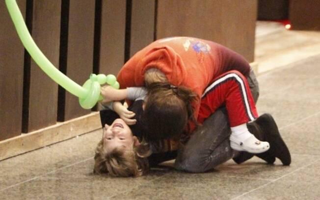 Fernanda Tavares senta no chão durante brincadeira com Lucas