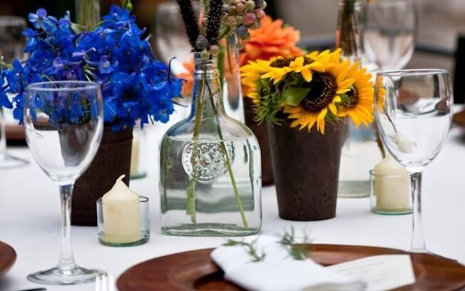 Use garrafas vazias como vaso de flor e velas para completar a decoração da mesa