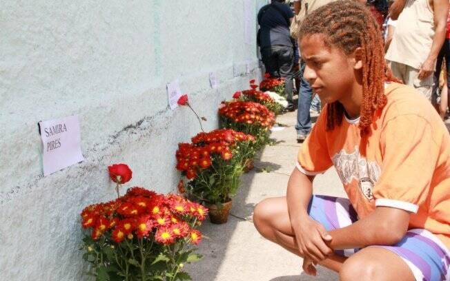 Aluno em frente ao muro da escola, coberto de flores para homenagear as vítimas