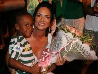 Luiza Brunet recebe flores das mãos de um garoto da comunidade