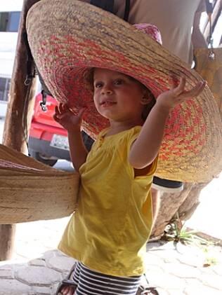 Julia no México, aos dois anos e meio, prova um sombrero