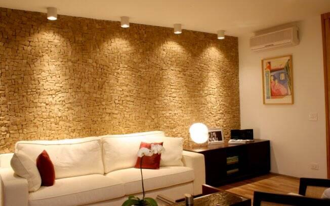 Na sala de TV, mosaico de pedras portuguesas na parede