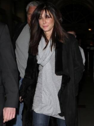 Sandra Bullock chega ao aeroporto de cachecol e casaco longo