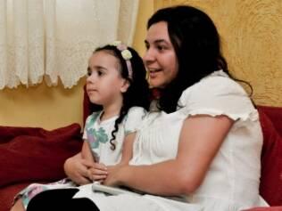 Alice e a mãe, Paula, assistem TV: