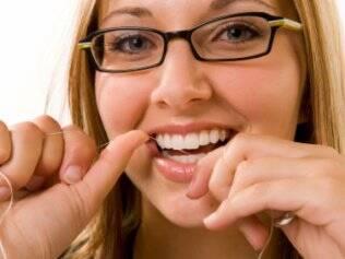 O uso diário do fio dental evita a placa e outros problemas
