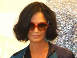 Luiza segura o riso enquanto posa com óculos de armação colorida