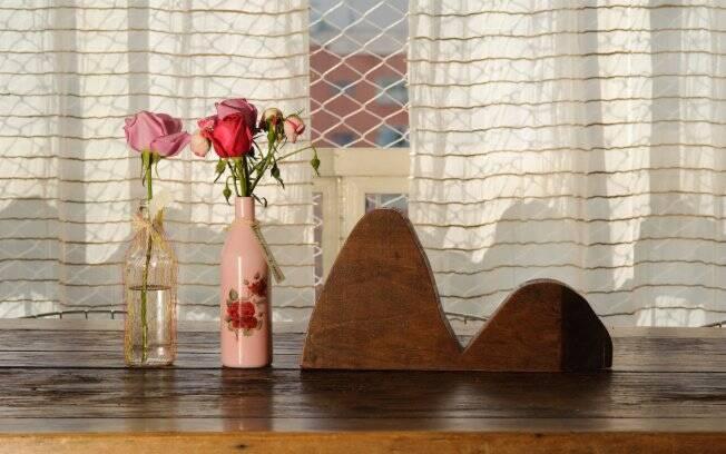 Para dar um toque especial à mesa da sala de jantar, Emanuelle utilizou garrafinhas d´água como vaso de flor e escultura em forma do Pão de Açúcar