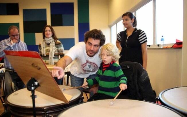 Thiago Lacerda e o filho Gael no ensaio da Sinfônica de Heliópolis. Ao fundo, Vanessa Lóes