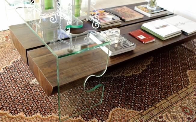 Ângela Tasca colocou um suporte de vidro recortado no canto da mesa de centro feita de madeira