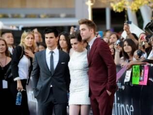 Taylor Lautner, Kristen Stewart e Robert Pattinson: o trio de protagonistas com o público ao fundo na premiere do filme