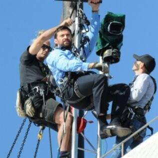 Hugh Jackman se prepara para voar do alto do Sydney Opera House e cair direto sobre o palco onde Oprah o aguarda