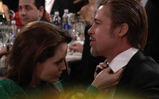 A atriz arruma a gravata do marido