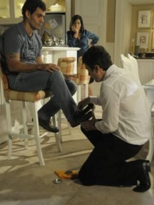 Léo engraxa os sapatos de Ismael, enquanto Norma assiste a tudo com um sorriso no rosto