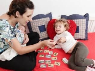 Karina brinca com Maria, a mais velha, enquanto segura o caçula Valentim