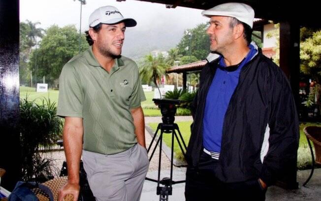Rodrigo Lombardi e Humberto Martins conversam enquanto aguardam passar a chuva no Rio de Janeiro