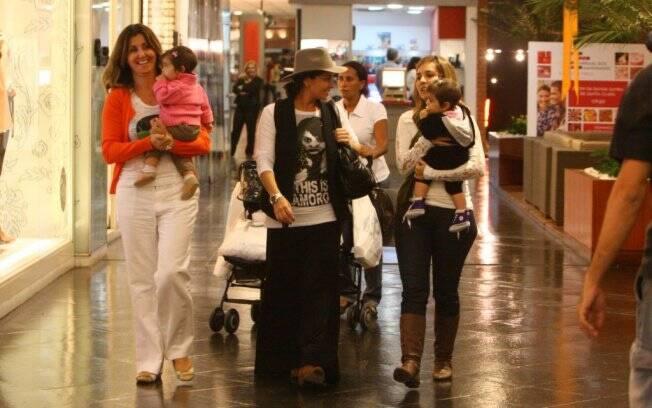 A tropa no shopping: Giovanna Antonelli com as filhas Antonio e Sofia, duas amigas e a babá, que carrega o carrinho duplo