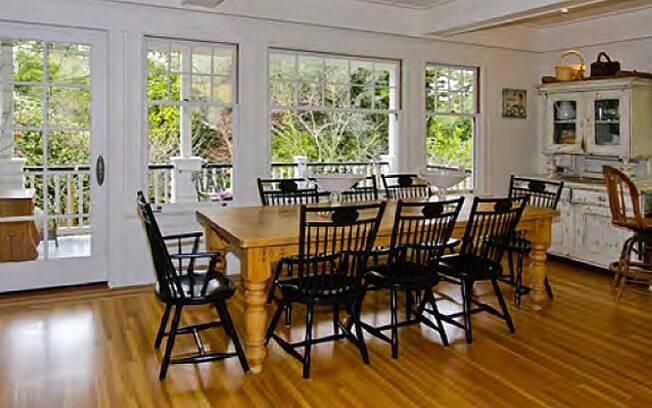 A sala de jantar é toda envidraçada, com vista para o jardim
