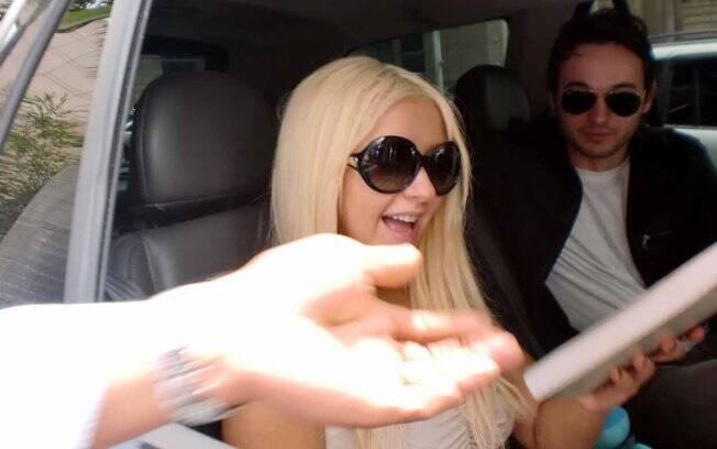Christina Aguilera distribui autógrafos ao deixar hotel, em São Paulo