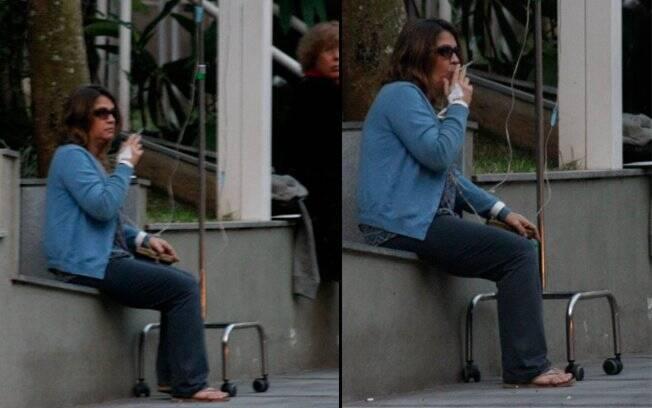 Com o soro aplicado na veia, Tássia Camargo fuma em frente ao hospital