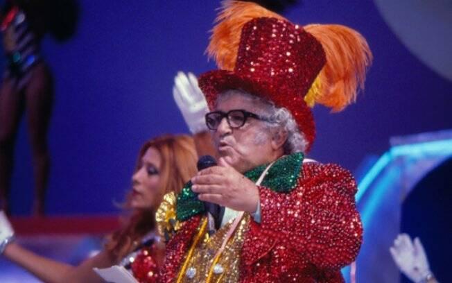 O apresentador Abelardo Barbosa, o Chacrinha. Ao fundo, Rita Cadillac