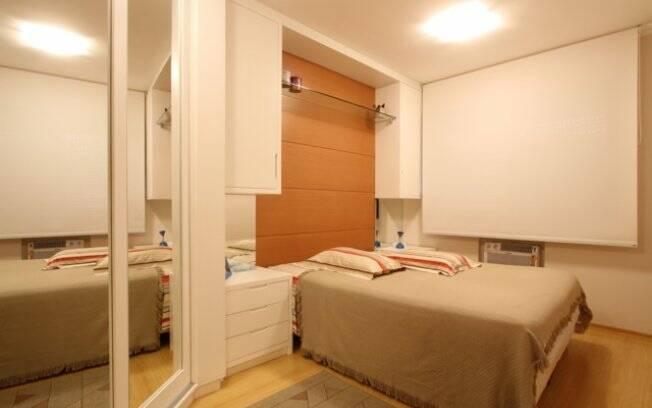 A cabeceira da cama vai do piso até o teto, ampliando o dormitório