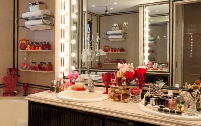 Um verdadeiro camarim no banheiro da arquiteta Brunete Fraccaroli. Espelho com lâmpadas ao redor e pia fechada para organizar os produtos de beleza