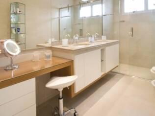 A bancada criada por Gerson Dutra de Sá serve de camarim no banheiro. No lado oposto, a estante de vidro abriga produtos de beleza
