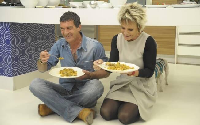 Depois de passar debaixo da mesa, Banderas e Ana Maria sentam no chão para comer