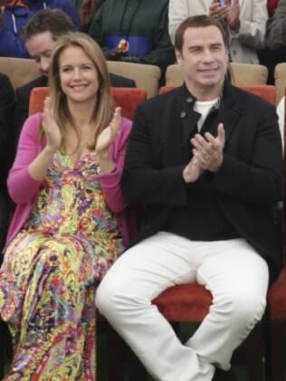 Na África do Sul, Kelly Preston exibiu a barriguinha ao lado do marido, o ator John Travolta
