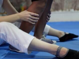 A fisioterapeuta segura os pés de Pamella: suporte distal