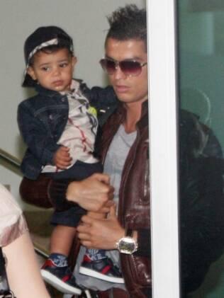 Cristiano Ronaldo Jr. de tênis e boné no colo do pai